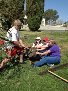 Wrestling with the Russian Olive tree to get it out of the 5 gallon container.Wyatt Wynn, Neeley Hartridge (Communication faculty), Sonette Russell (Forestry student transferring to Humboldt State), Janet Tarjan (Math faculty)Planting 50 of the 100 trees on March 23, 2013 at Bakersfield College to celebrate the Centennial Year