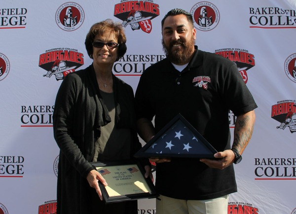 KCCD Board of Trustees member Kay Meek presents a ceremonial American flag to BC Veterans advisor Armando Trujillo.