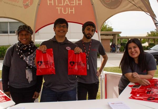 学生健康与健康咨询委员会的成员在4月18日举行的叛徒脉冲健康博览会期间,在健康小屋内摆出姿势。