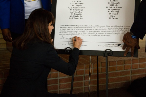 Sonya signing the agreement