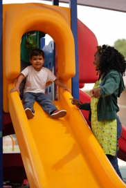 teacher helping a young child on slide