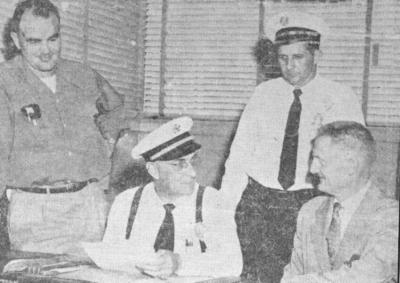 办公室里四个穿黑白新闻纸的人