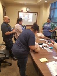 在假人上学习心肺复苏术的员工