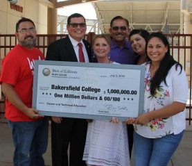 Rudy Salas and the CTE Team hold a large check for $1 million.