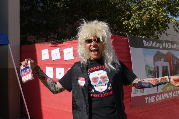 Costumed in blond wig, tattooed arms and snake name tag