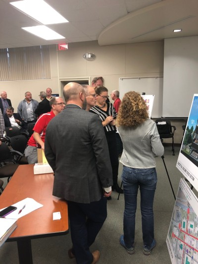 Faculty and staff looking at the design poster