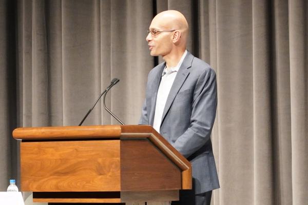 Manny Mourtzanos speaking at the podium