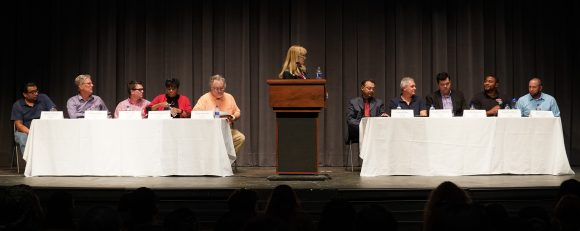 Mary Jo at the podium with panels on either side