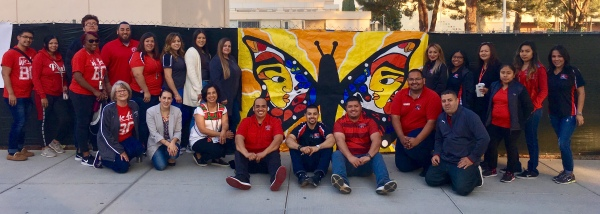 Students and staff in front of a large butterfly poster