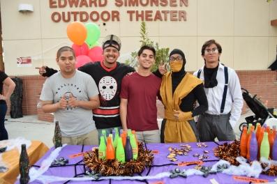 4名学生在一张桌子上摆出五颜六色的瓶子