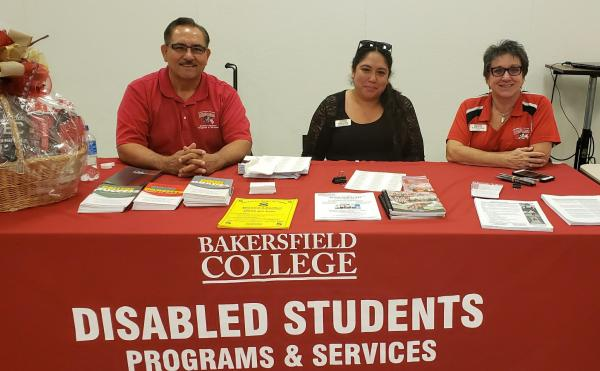 DSPS staff pose at table with brochures