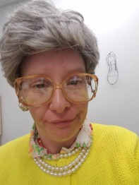Woman with grey wig, larger glasses, pearl necklaces, yellow sweater and smirk on her face