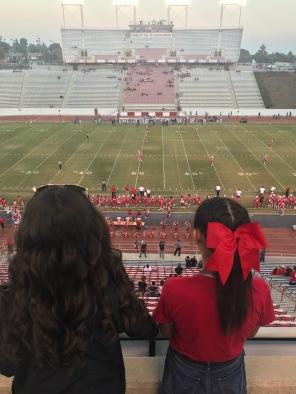 比赛期间,头上扎着红色大丝带的女孩俯瞰着体育场和球场。