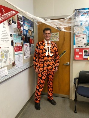 Jon Brown in a pumpkin covered suit with the Pi symbol on the front