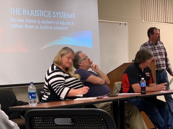 """Panel in front of the screen that says """"The Injustice System? Do we have a system of injustice rather than a Justice system?"""""""