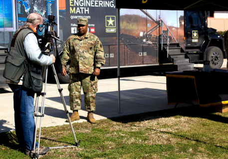 A cameraman from KERO gets ready to interview a US Army soldier on the air in front of the STEM truck parked in the Renegade Food Court area.