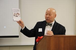 Lance Izumi holding up his book