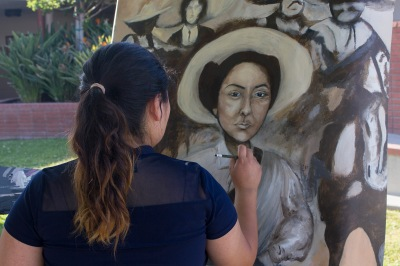 Girl painting portrait of woman