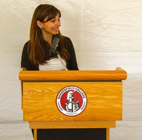 Sonya speaking and smiling at the lectern with the Bakersfield College seal.