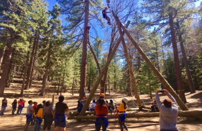 Students watch as a student climbs ropes into the trees.