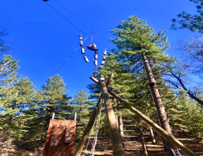 Student zip lines from one tree to another.