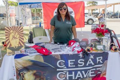 women standing and smiling at cesar chavez booth
