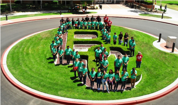Ag camp students in matching t-shirts around the BC shaped hedge.
