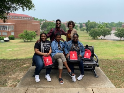 4 students with Dr. Parks with the campus as a backdrop.