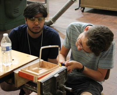 Assistant observes student sawing his cigar box.