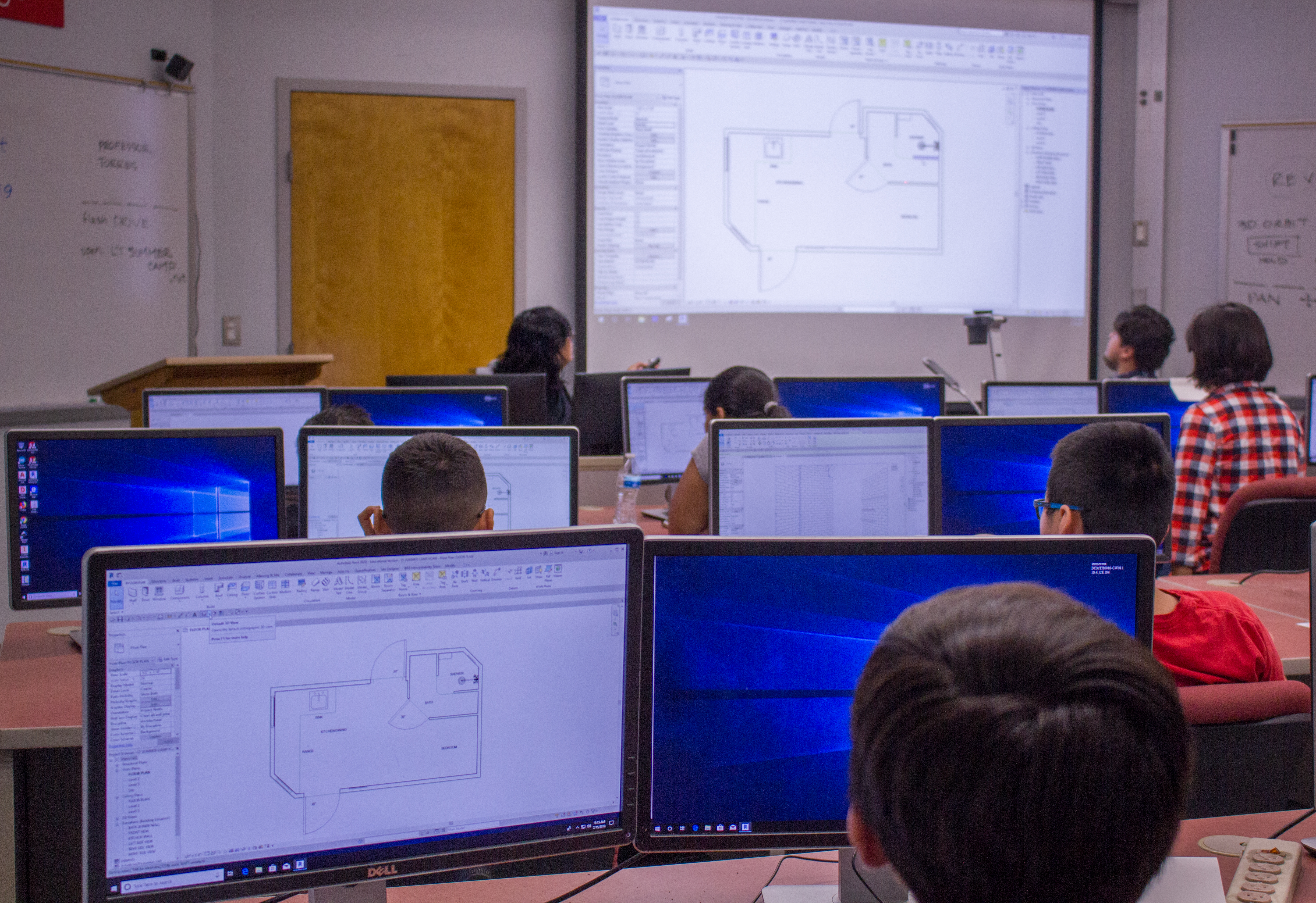 Students at desks looking at computer screens with architecture plans.