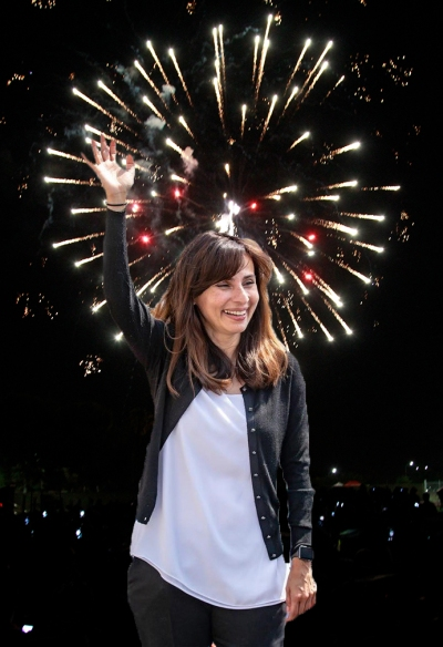 Sonya waving in front of fireworks.