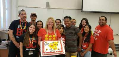 Students and staff around a large cake.