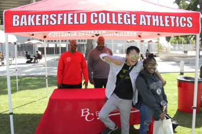 Students smiling and pointing in front of the BC Athletics tent.